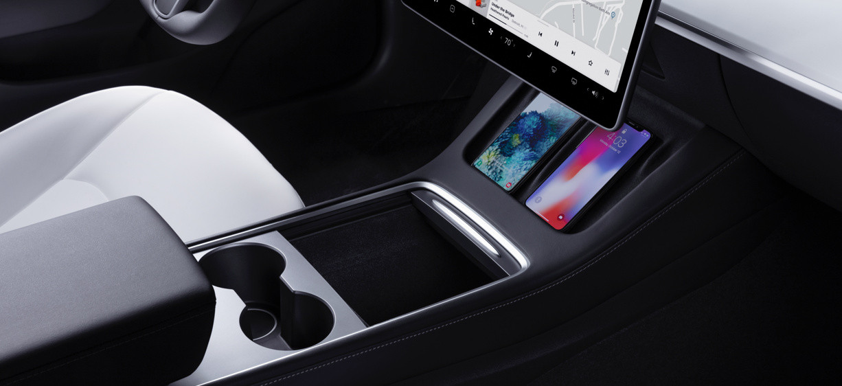 "Model 3 interior with cup holder, 15"" touchscreen, cell phones"
