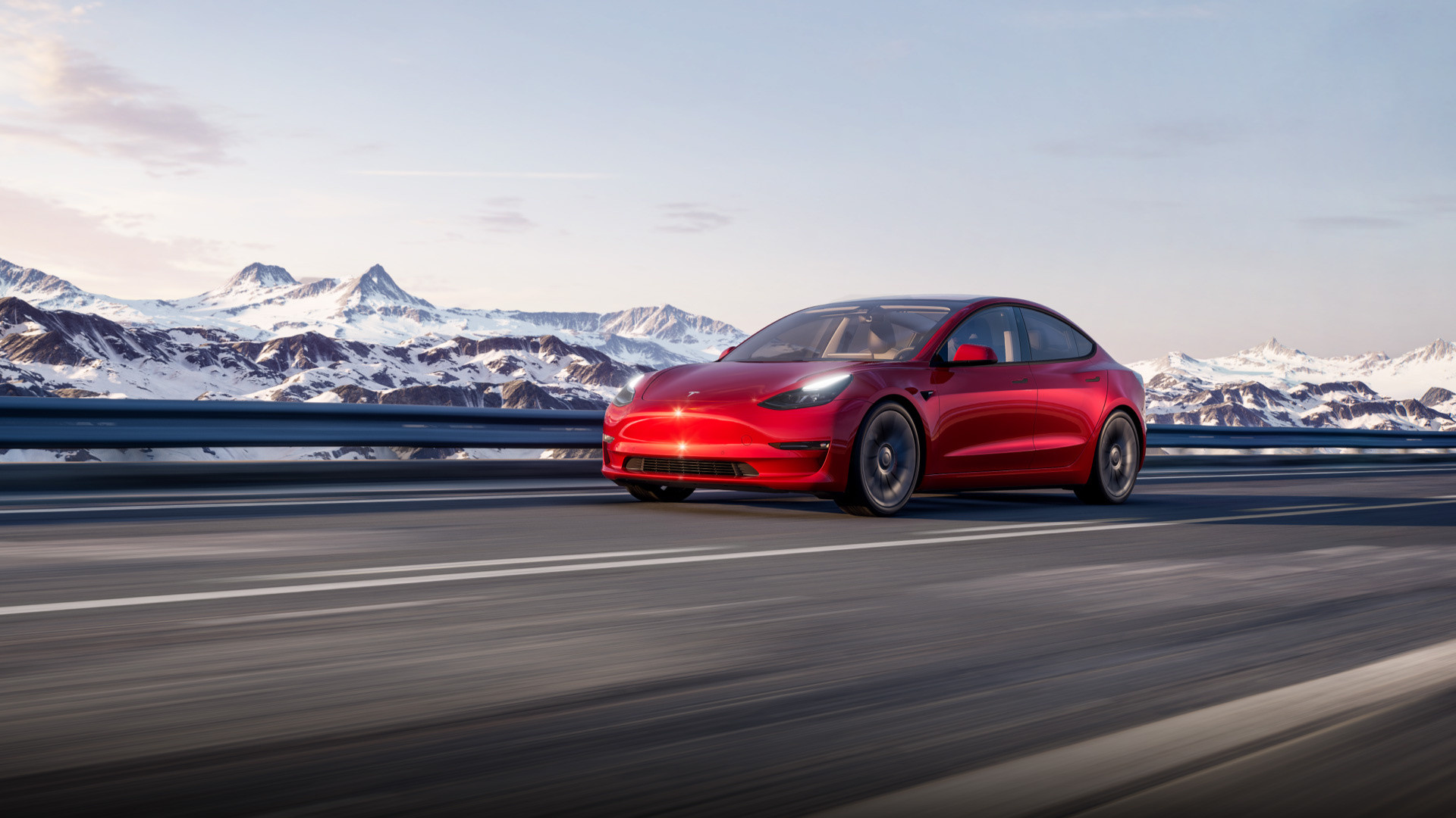 Red Model 3 driving down a mountainside road