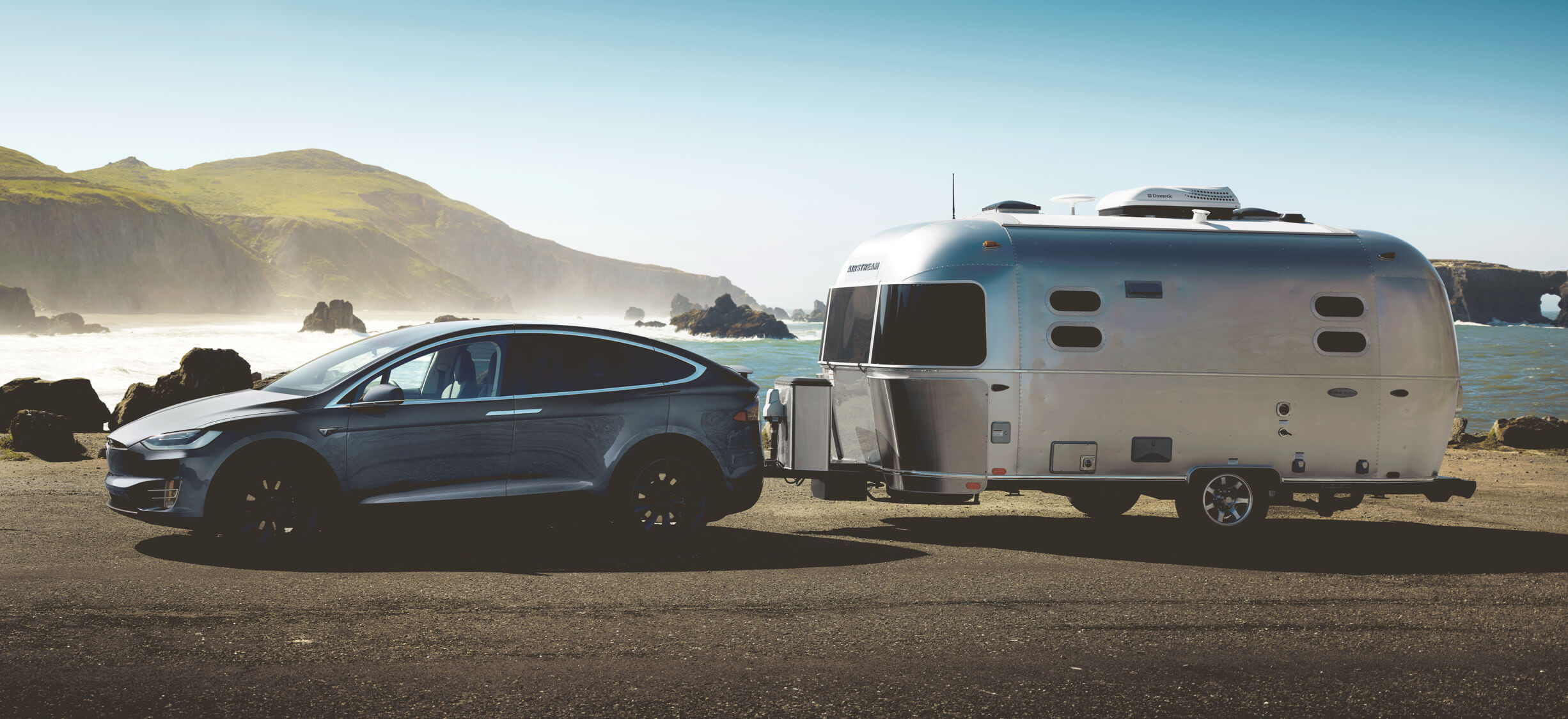 Midnight silver metallic Model X towing a silver travel trailer