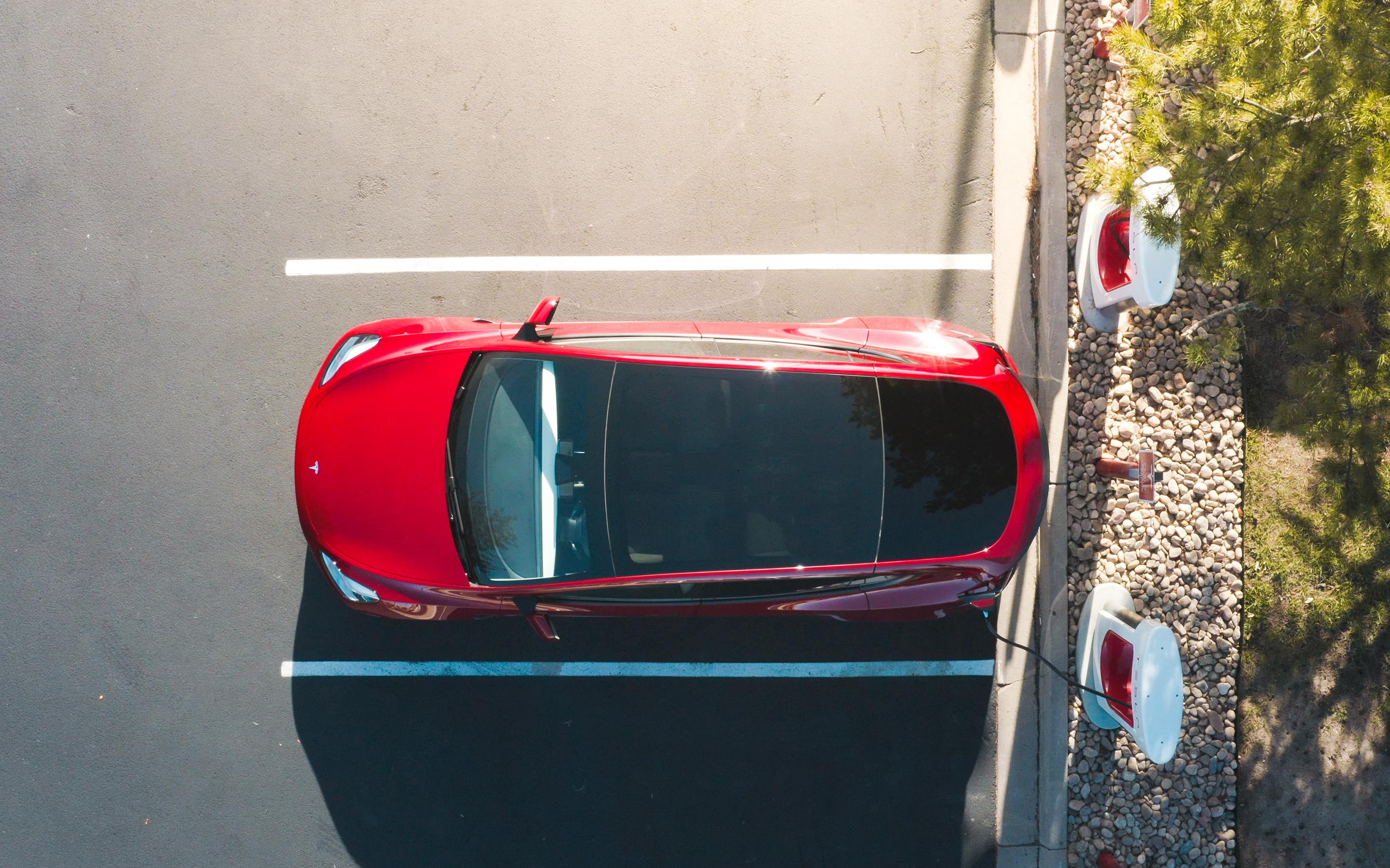 Birds-eye view of red Tesla charging via Supercharger