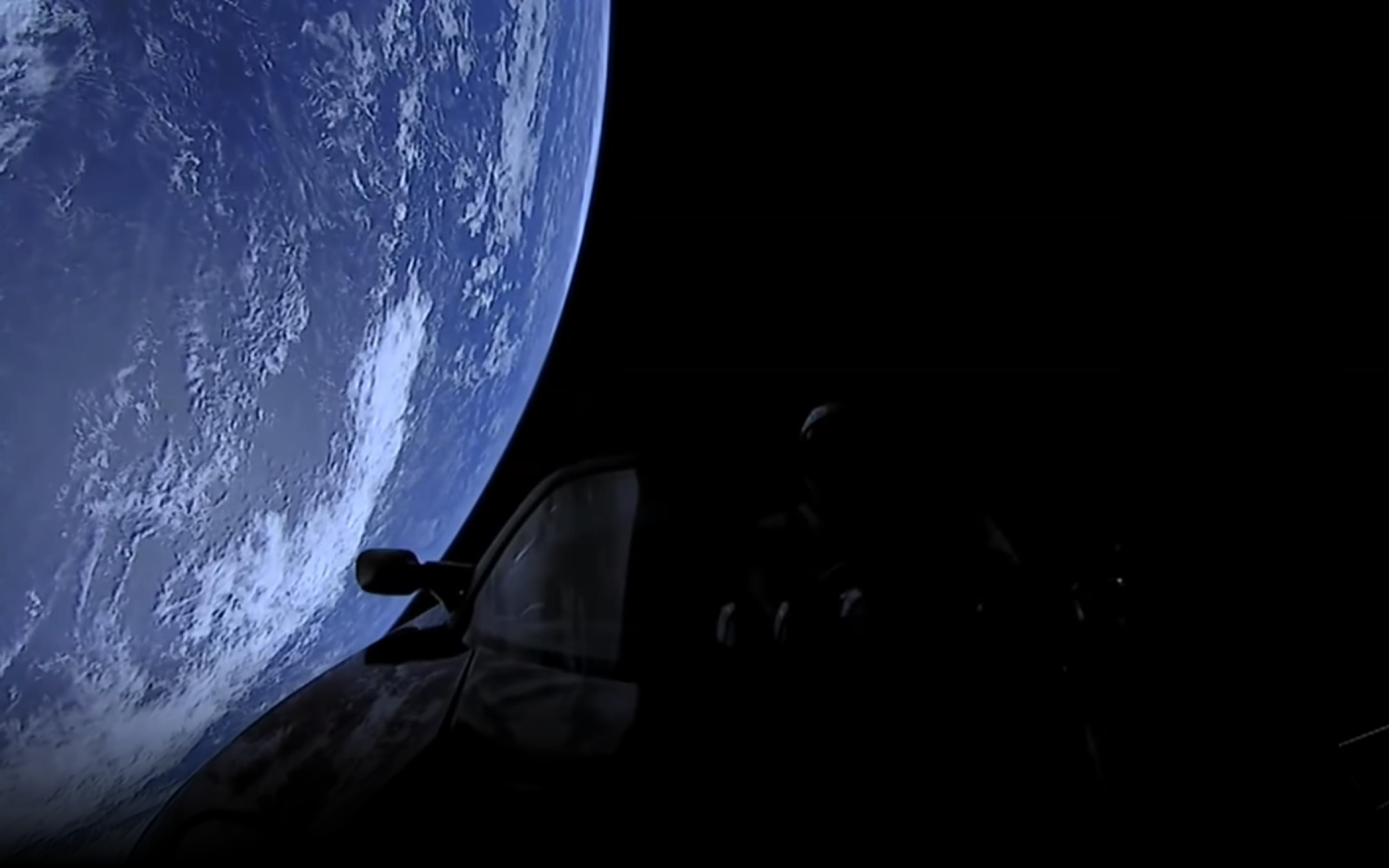 Silhouette of a Roadster in space flying over Earth