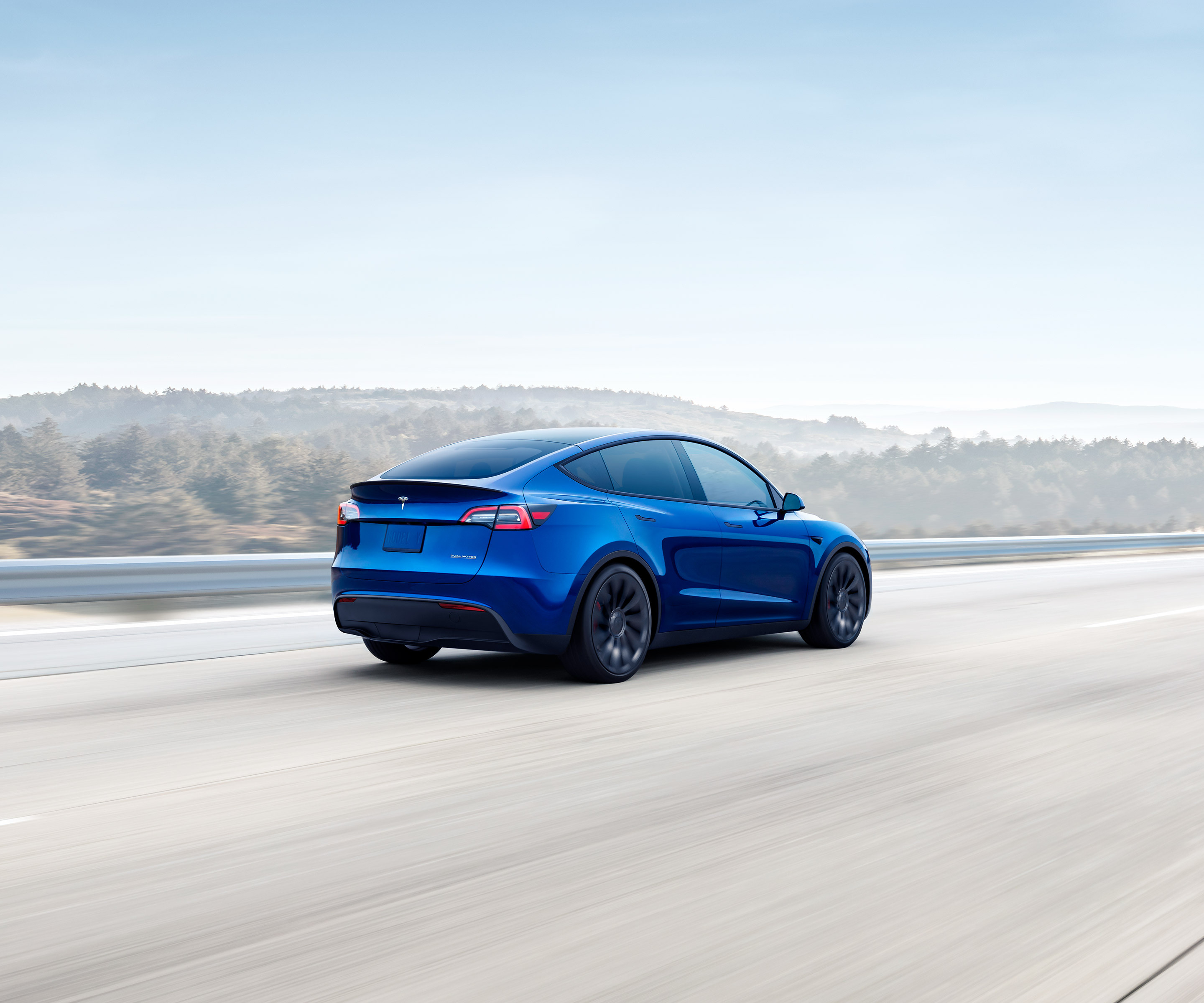 Metallic blue Model Y driving down a hillside highway