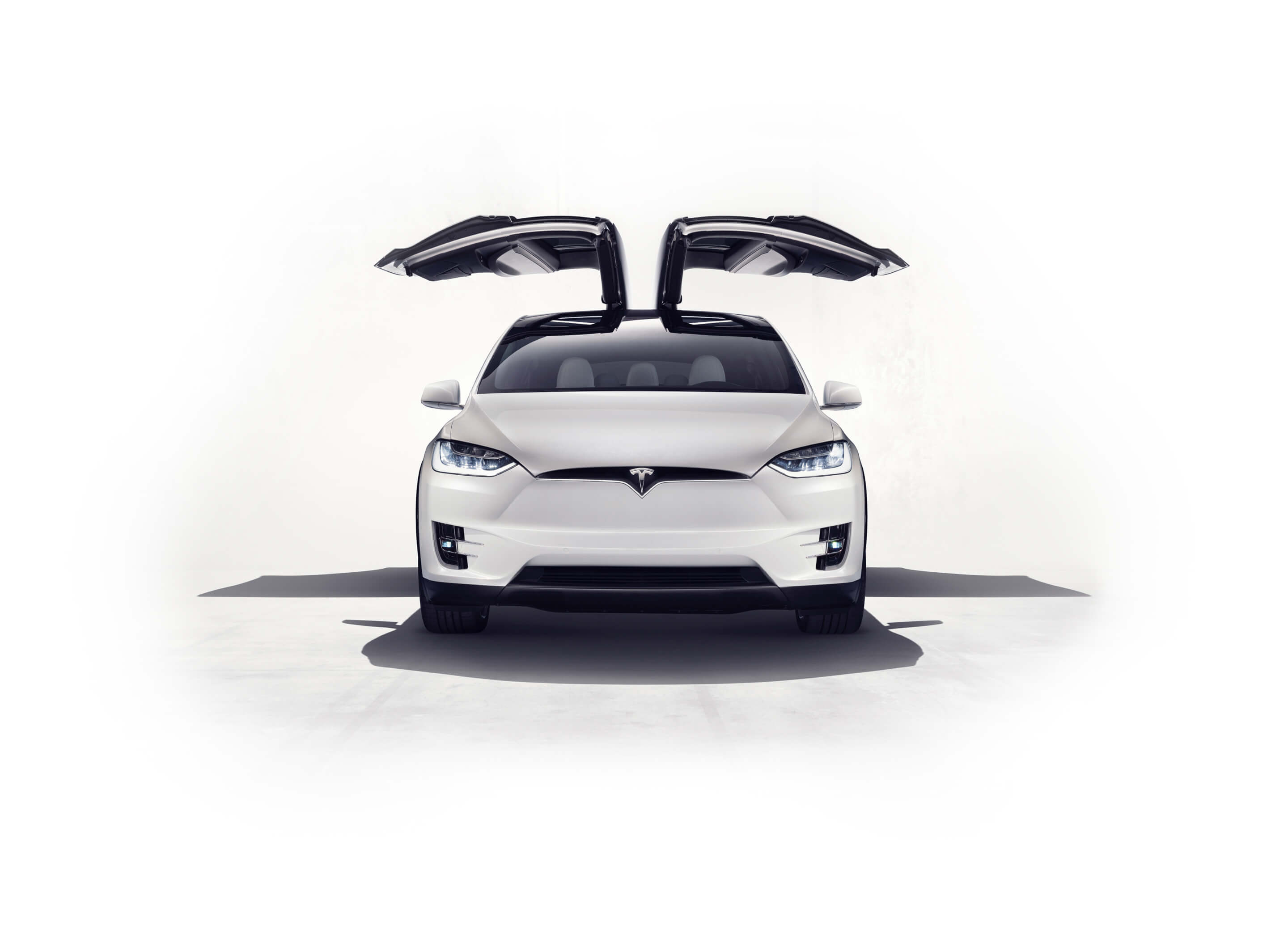 Front view of white Model X with falcon wing doors open