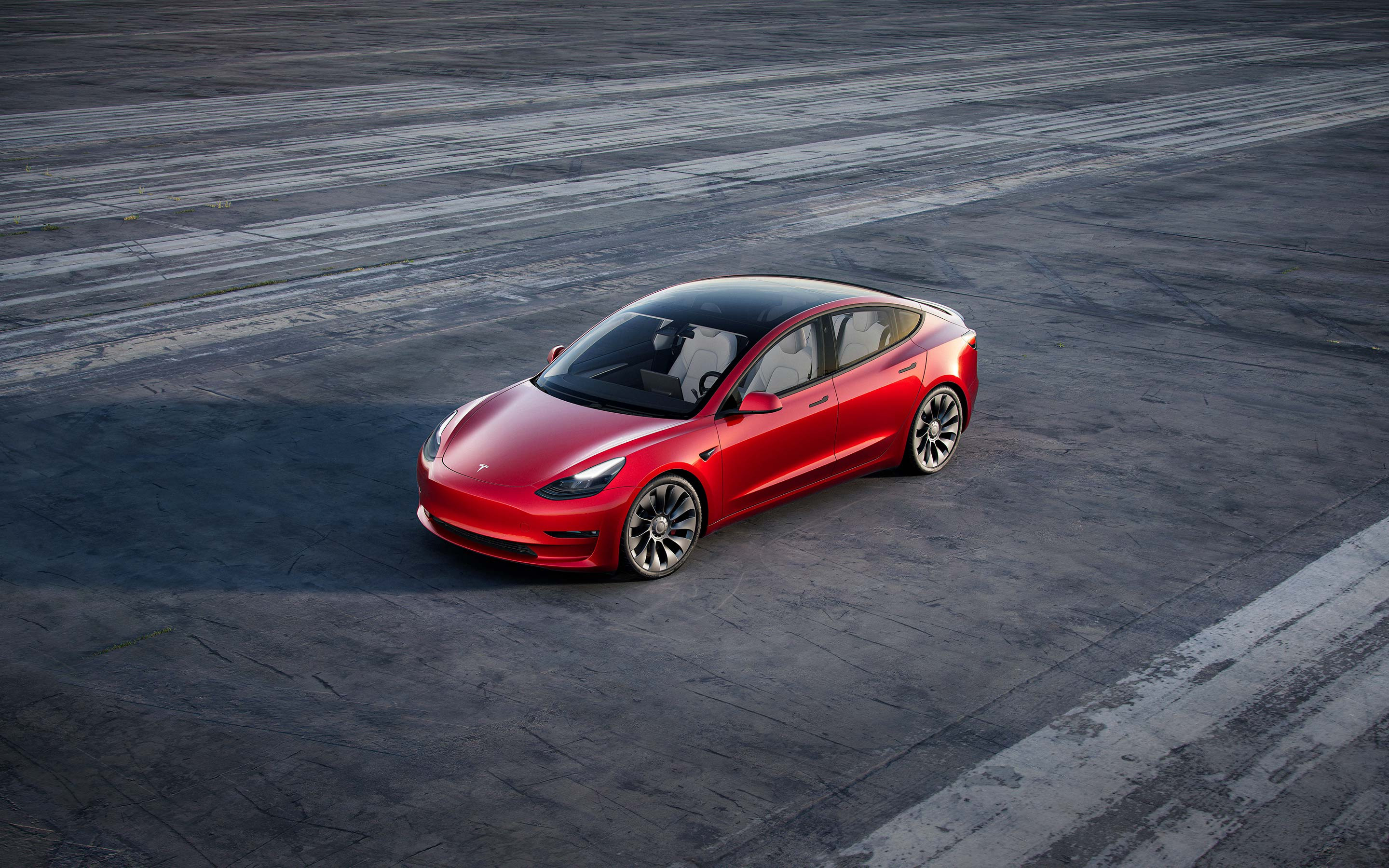 Birds-eye view of red Model 3 on gray asphalt