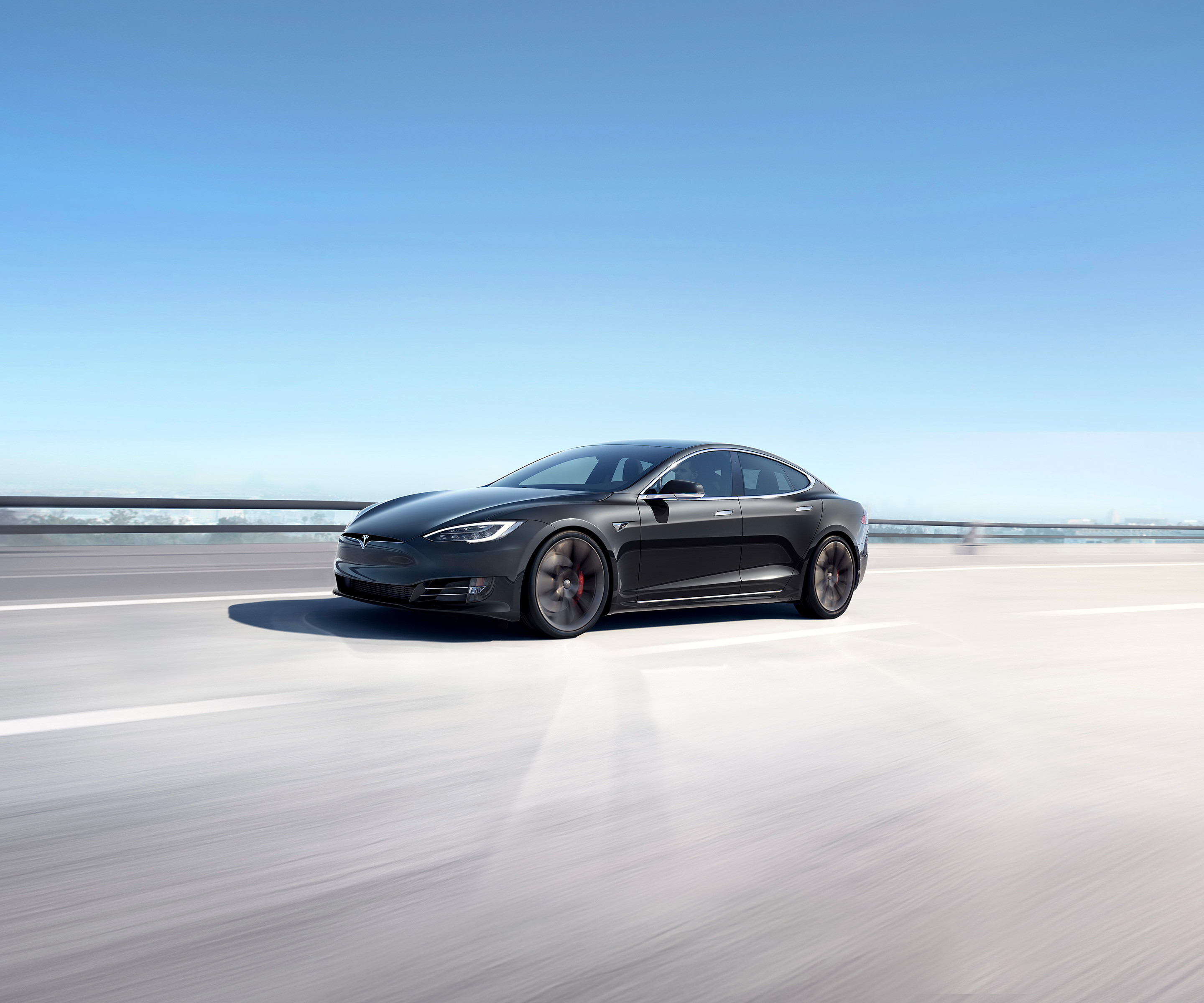 Solid black Model S accelerating on an elevated highway