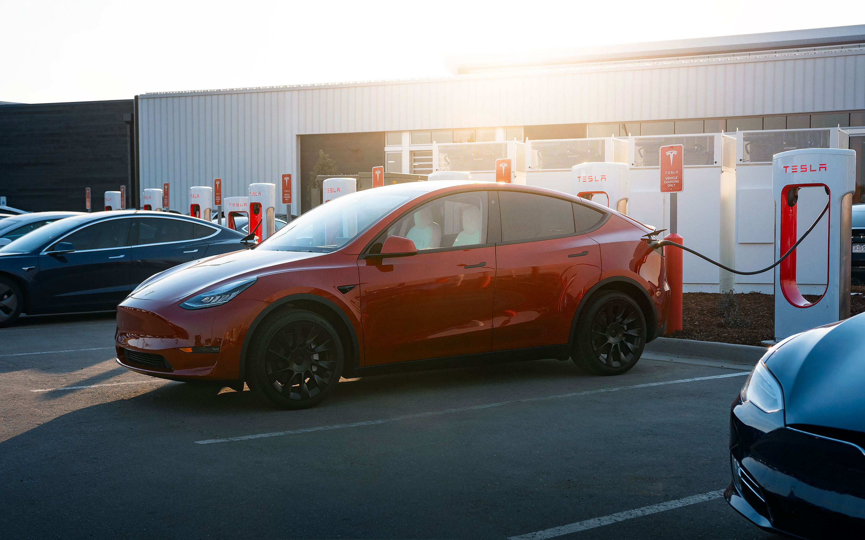Red Model Y charging via Supercharger in a parking lot