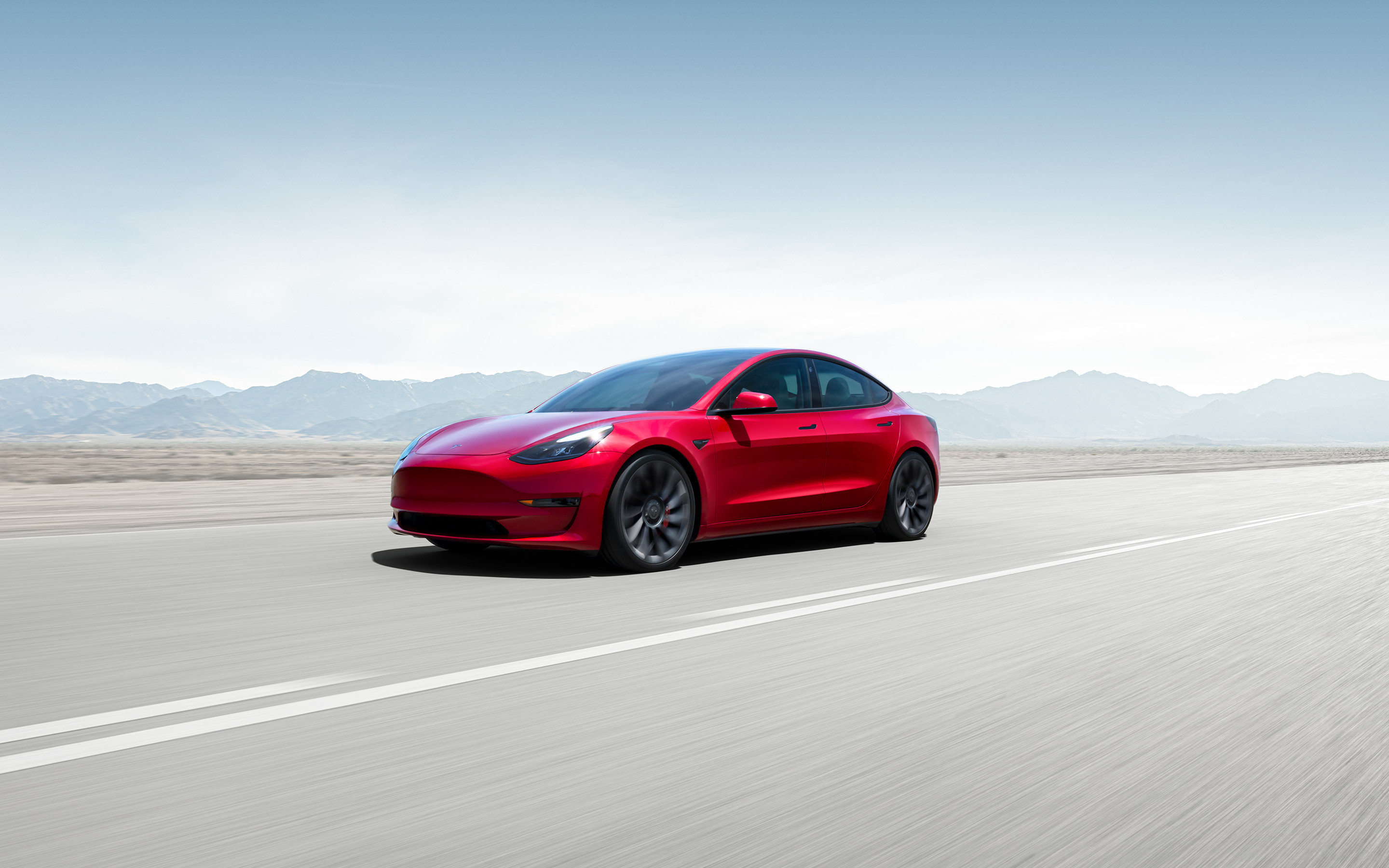 Red Model 3 parked on weathered concrete in front of a cityscape