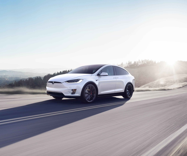 Biserno beli Model X, ki vozi po gorski cesti