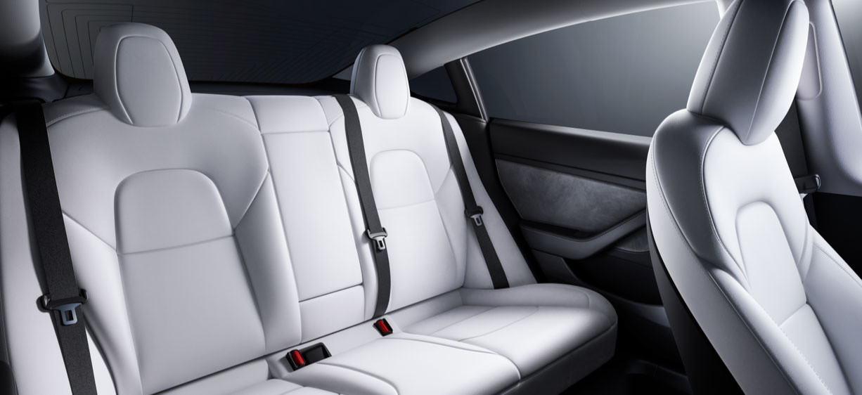 View of the spacious backseat of a Model 3 with white interior